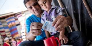 En sittande man river upp en liten påse vätskeersättning och häller i en röd kopp till en liten pojke.