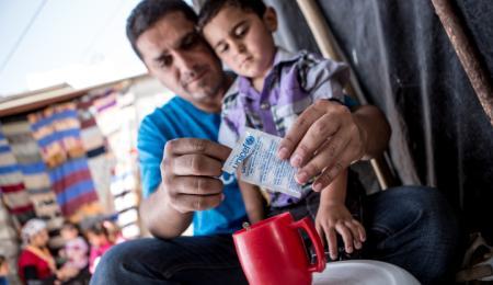 Man river upp en påse vätskeersättning och häller i en röd kopp till en liten pojke.