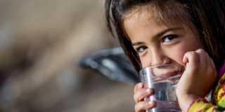 Flicka dricker vatten ur glas.